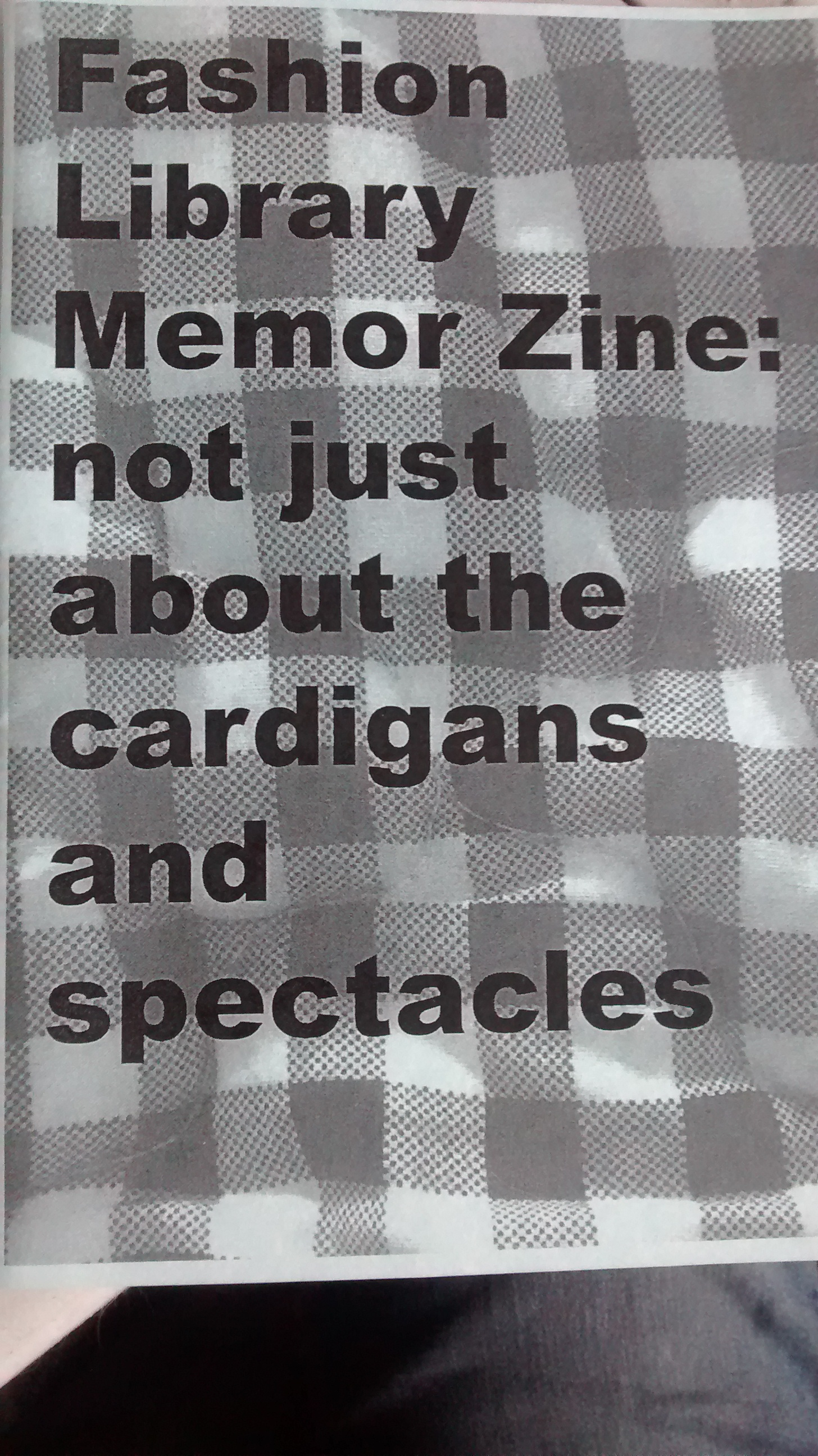 "Title, ""Fashion Library Memor Zine: not just about the cardigans and spectacles"" printed over half-toned photograph of checkerboard tablecloth."