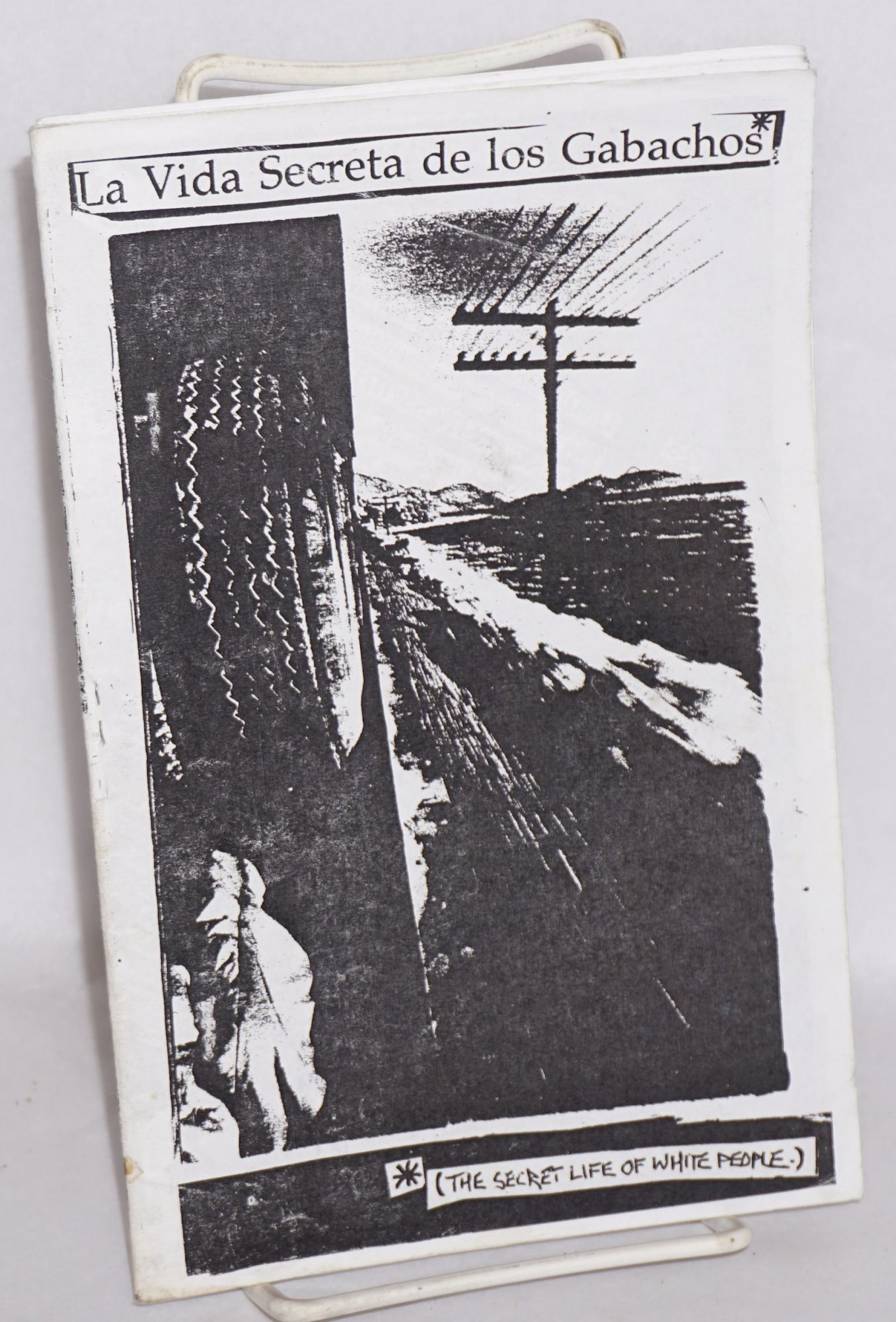 The title in Spanish is across the top, and in English along the bottom.  Black and white collage of a tire on the left and telephone pole and wires on the right.