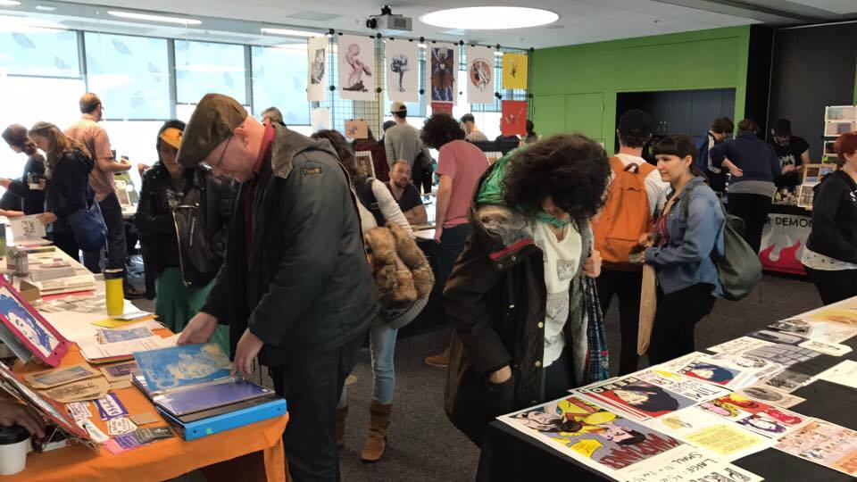 People looking at zines at the zine fair