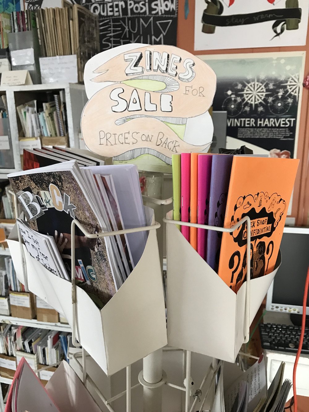 "A rack displaying zines reads ""Zines For Sale"""